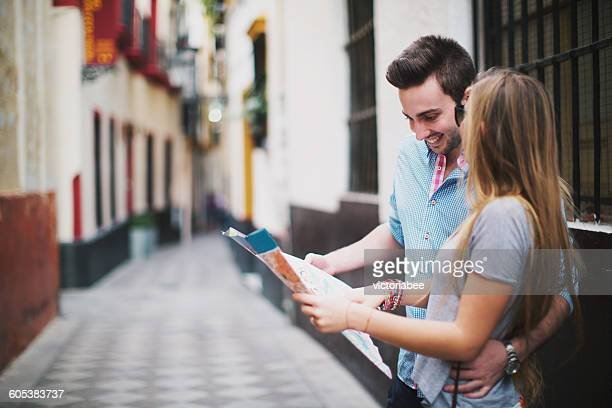 Young couple sightseeing in city with map, Seville, Spain