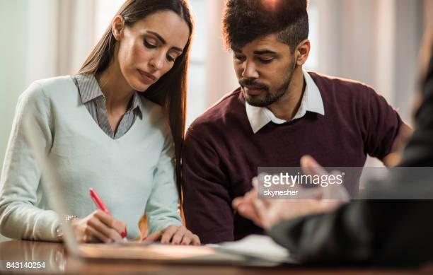 Jeune couple de signer un contrat sur une rencontre avec le conseiller en assurances.