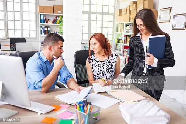 Young couple signing papers in modern office