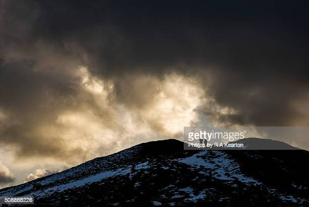 a young couple silhouetted on the summit of mam tor in winter - peak district national park stock pictures, royalty-free photos & images