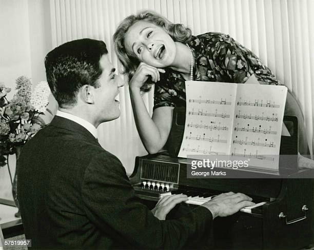 Young couple singing, man playing piano, (B&W)