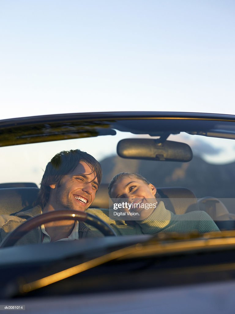 Young Couple Sit in the Front of a Convertible, Laughing : Stock Photo
