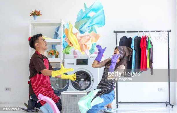 young couple sit next to a washing machine at home. they laugh and embrace while loading the washer with dirty laundry. - chores stock pictures, royalty-free photos & images