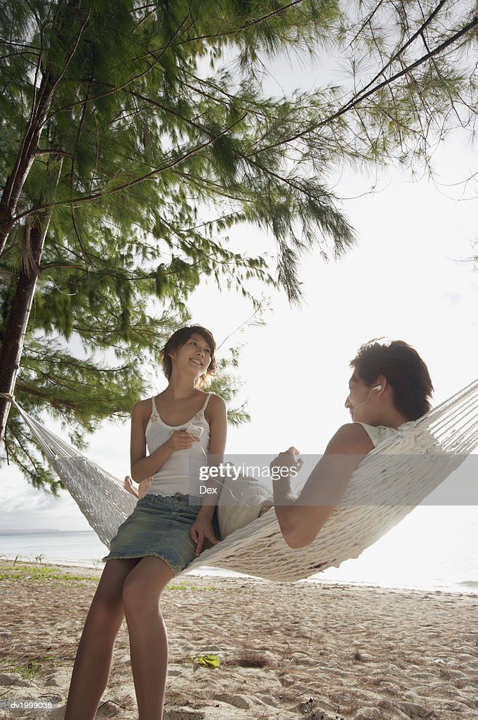Young Couple Sit on a Hammock on the Beach Listening to Music on Headphones : Stock Photo