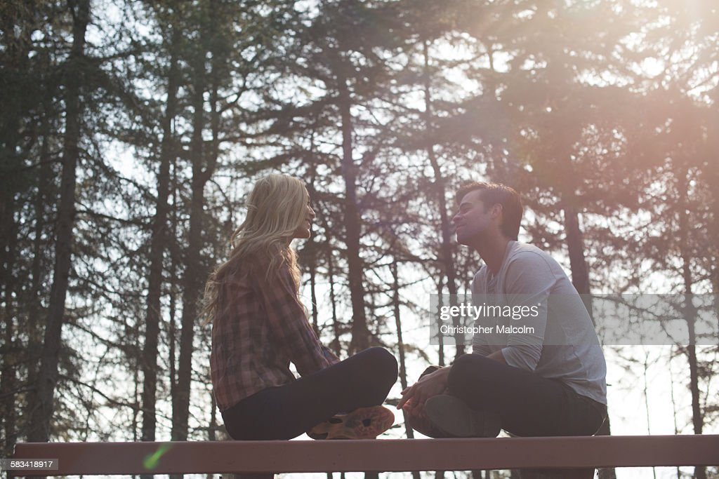Young couple sit on bench in woods : Stock Photo