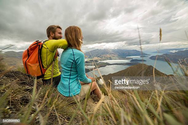 Young couple sit on mountain top and look at view