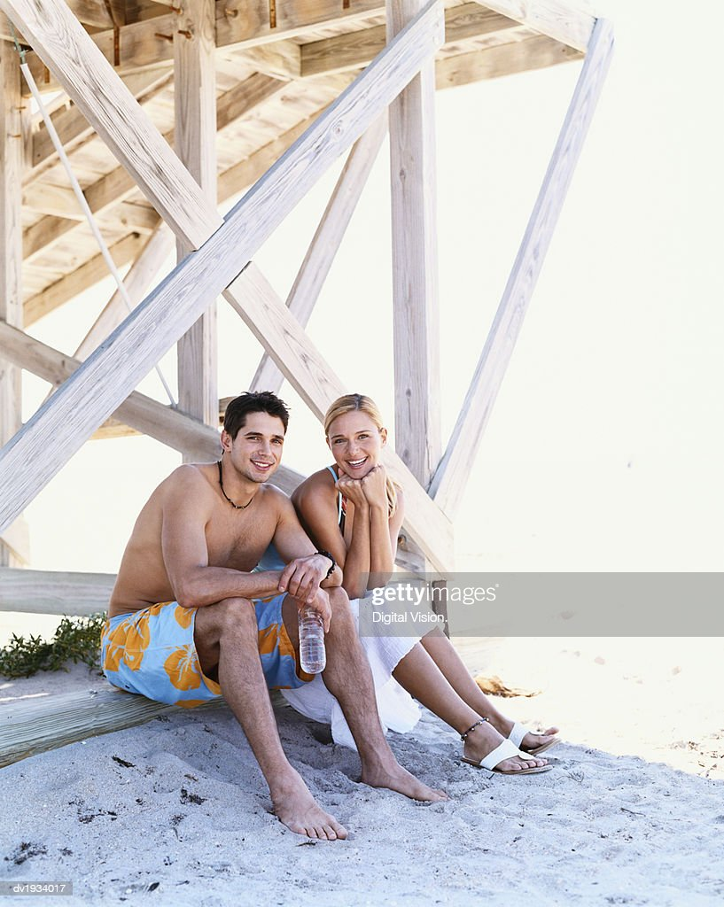Young Couple Sit on the Beach Under a Wooden Pier : Stock Photo