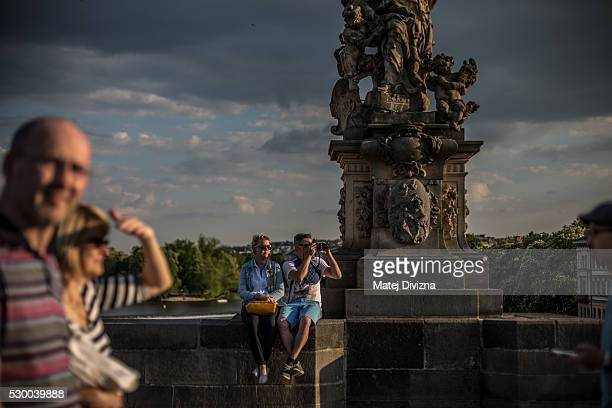 A young couple sit on the Charles Bridge on May 9 2016 in Prague Czech Republic The Charles Bridge construction began in 1357 by Charles IV's builder...