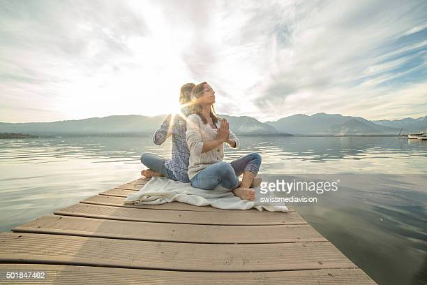 Young couple sits on jetty above lake, exercises yoga