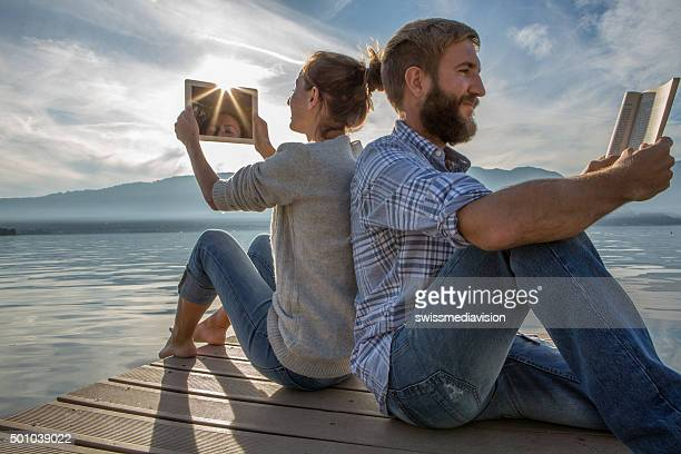 Young couple sits on jetty above lake, uses book/digital tablet