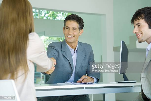 Young couple sitting across desk from businessman, woman shaking hands with businessman