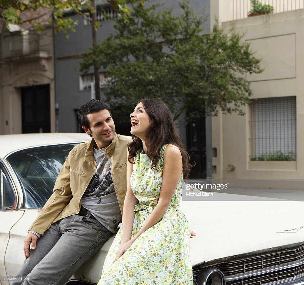 Young couple sitting against car, smiling : Stock Photo