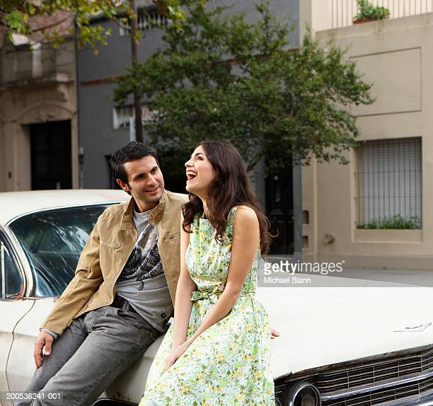 Young couple sitting against car, smiling