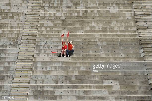 young couple sitting alone in bleachers - empty bleachers stockfoto's en -beelden