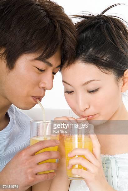 Young couple sitting and drinking orange juice