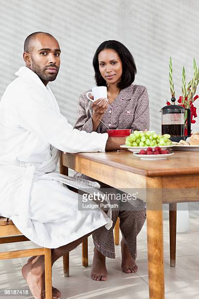 a young couple sitting at a table for breakfast - barefoot black men stock pictures, royalty-free photos & images