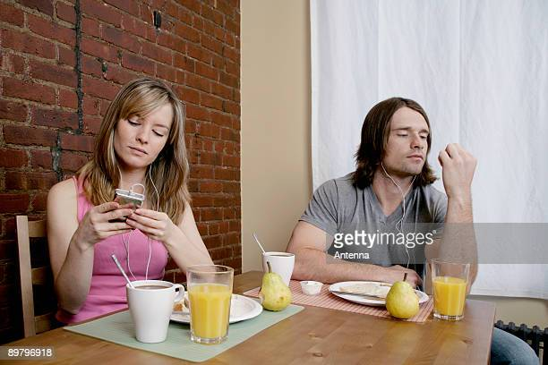 a young couple sitting at breakfast listening to mp3 players - mp3 juices stock photos and pictures