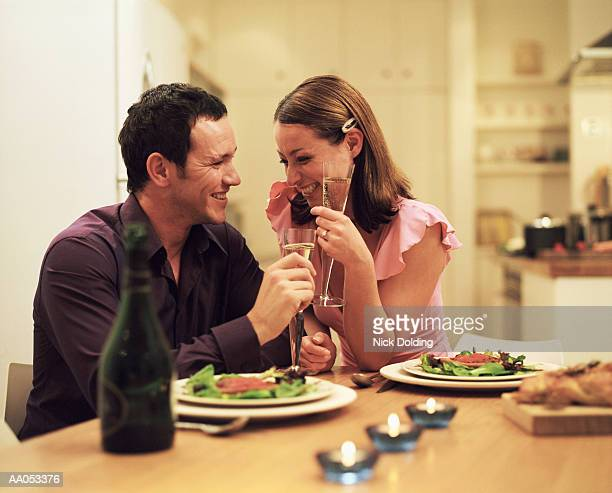 Young couple sitting at dining table, drinking champagne, laughing