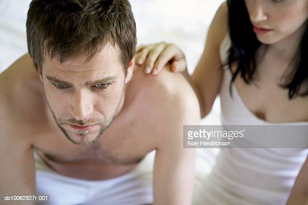 Young couple sitting at edge of bed, man worried, high angle view