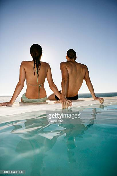 Young couple sitting at edge of outdoor swimming pool, rear view