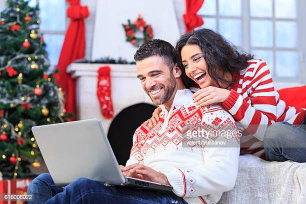 Young couple sitting at home and using laptop