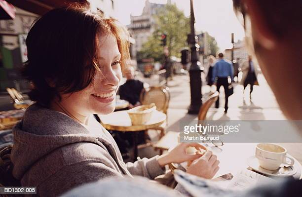 Young couple sitting at outdoor cafe, close-up, Paris, France
