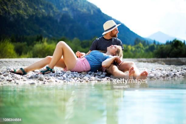 young couple sitting at riverside - ventenne foto e immagini stock