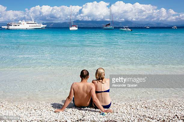 Young couple sitting at the beach, rear view