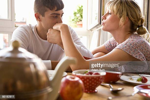 A young couple sitting at the breakfast table