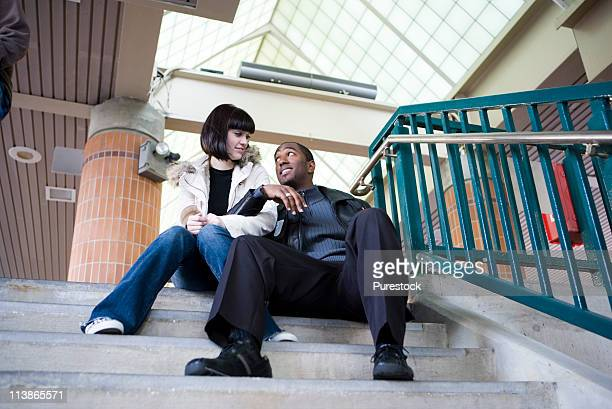 Young couple sitting at the top of a flight of stairs