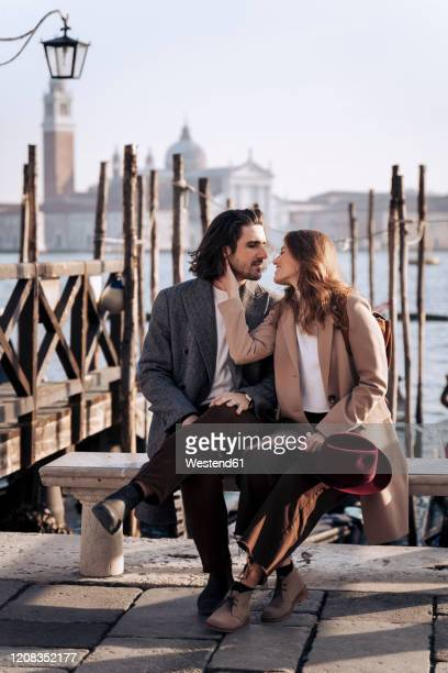 young couple sitting at the waterfront in venice, italy - laguna foto e immagini stock