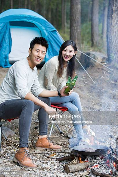 Young couple sitting beside campfire preparing food