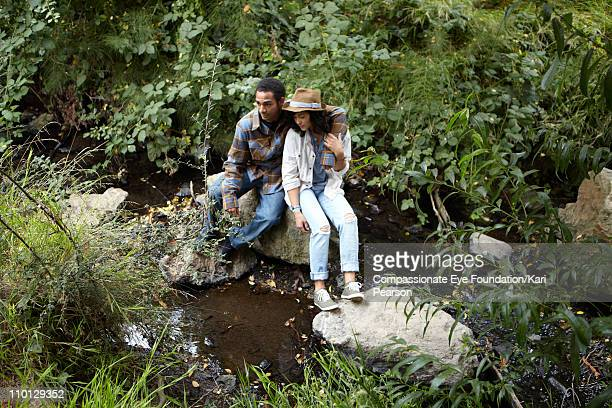Young couple sitting by a stream