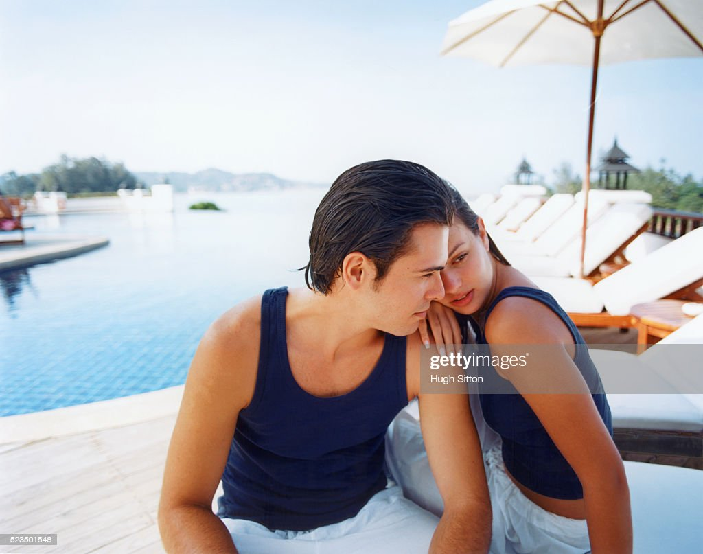 Young couple sitting by the pool : Stock Photo