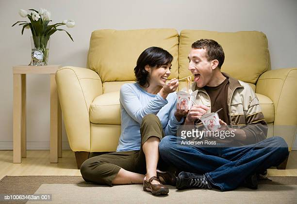 Young couple sitting cross-legged in front of sofa eating takeaway food, woman feeding man with chopsticks, at home