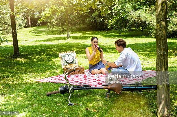 young couple sitting eating picnic on blanket - picknick stock-fotos und bilder
