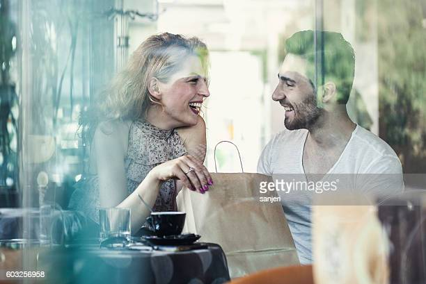 Young Couple Sitting in a Cafe Chatting
