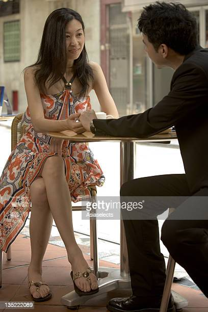 Young couple sitting in a cafe holding hands