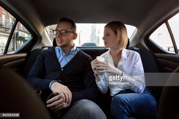 Young couple sitting in back of car