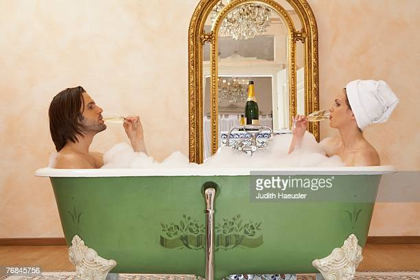 young couple sitting in bath drinking champagne, side view - couple bathtub stock pictures, royalty-free photos & images