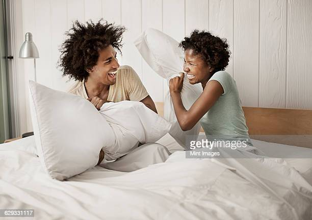 A young couple sitting in bed, playfighting with pillows.