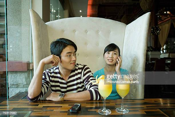 Young couple sitting in booth, woman using cell phone