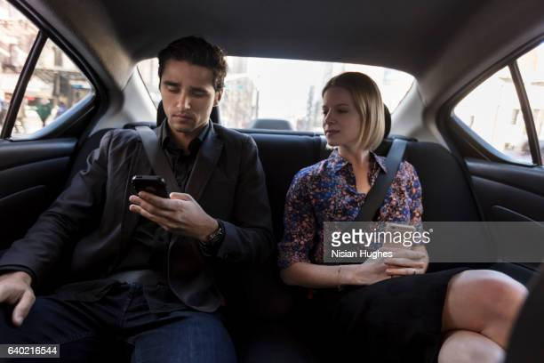 Young couple sitting in car on phones