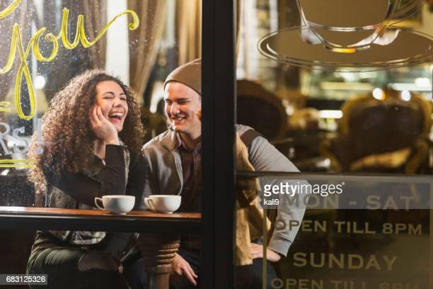 Pareja de jóvenes sentados en la cafetería hablando, riendo