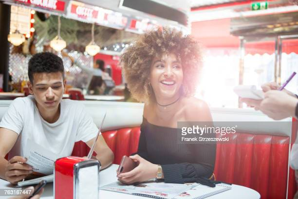 Young couple sitting in diner giving order to waitress