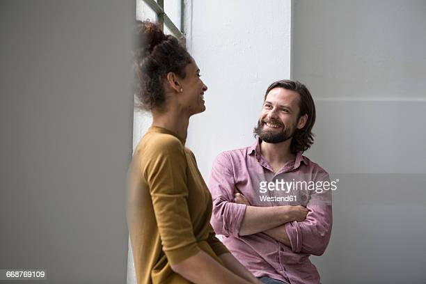 Young couple sitting in flat and talking to each other