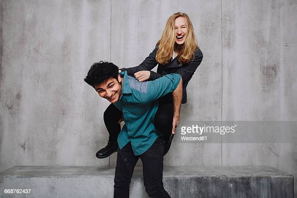 Young couple sitting in front of concrete wall, piggyback