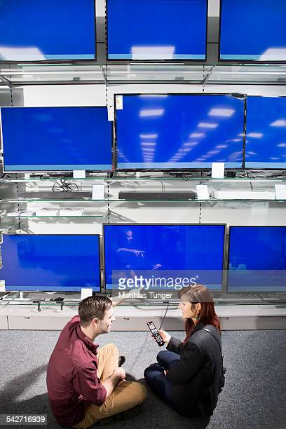 Young couple sitting in front of new TVs