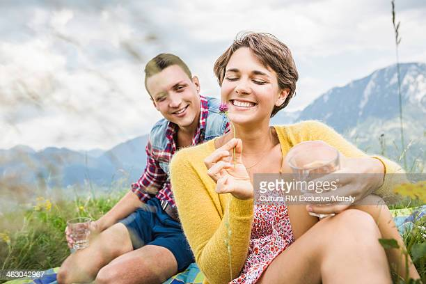 Young couple sitting in meadow, Tyrol, Austria