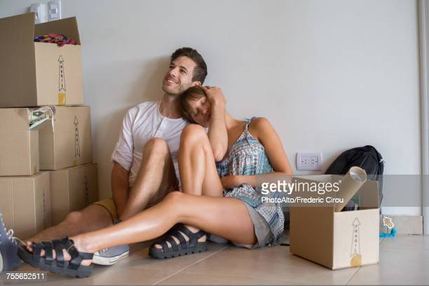 young couple sitting in new house with cardboard boxes - unpacking stock pictures, royalty-free photos & images